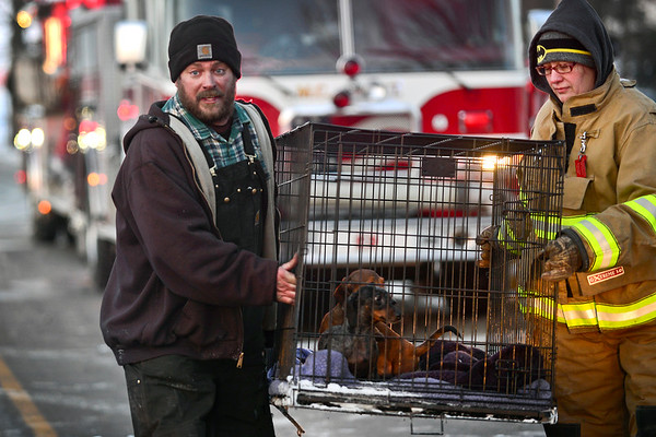 BEN MIKESELL | THE GOSHEN NEWS<br /> David Miller carries two of his dachshunds, Morgan and Maggie, with the help of Melanie Webb from Millersburg Clinton Fire Territory after his house burned Tuesday in Millersburg. Miller said he noticed the fire when he pulled into his driveway, and went in to rescue the family's four dogs. Miller escaped with three of the four dogs. The last dog, Ginger, was successfully rescued when first responders entered the home.