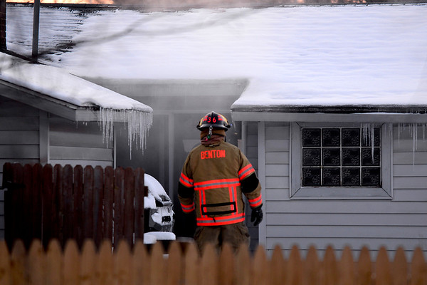 BEN MIKESELL | THE GOSHEN NEWS<br /> A firefighter from Benton Township Fire Department enters a home on fire Tuesday at 318 N. Benton St. in Millersburg.