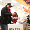 LEANDRA BEABOUT | THE GOSHEN NEWS<br /> Assistant deli manager Jeanette Johnston deposits new winter hats into the Share the Warmth donation bin at the Martin's Super Market on Bashor Rd.