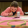 BEN MIKESELL | THE GOSHEN NEWS<br /> Twelve-year-old Maddie Hershberger focuses as she paints onto her screen print during Maker Monday at the Goshen Public Library. Once a month, Maker Monday focuses on a different theme for students to make creations. This month, Teen Services Coordinator Emily Stuckey Weber taught the group how to make screen prints for shirts.