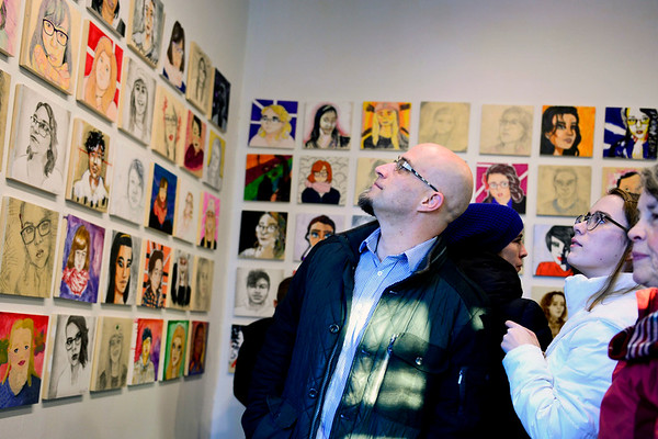 BEN MIKESELL   THE GOSHEN NEWS<br /> Nick Borden looks for his daughter, Estella, in the gallery of portraits on display Friday at Goshen Youth Arts. Estella, a freshman at Goshen High School, painted nine portraits of the other students in the project, and they did the same, totalling 90 portraits on display.
