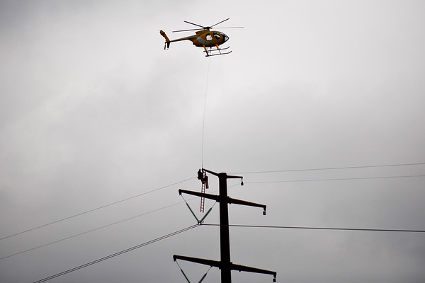 BEN MIKESELL | THE GOSHEN NEWS<br /> A helicopter hoists a construction worker up to a power line Saturday near C.R. 127 south of U.S. 6.