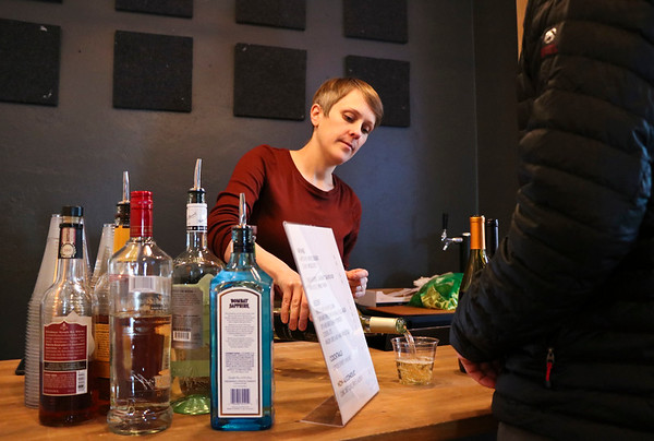 LEANDRA BEABOUT | THE GOSHEN NEWS<br /> Blank Space owner Anna Wiebe pours a glass for a patron of the venue's pop-up bar. Visitors were invited to enjoy the cozy space, which was lit with a variety of candles, light therapy lamps and Himalayan salt lamps.
