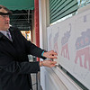 Roger Schneider | The Goshen News<br /> Goshen City Council president Brett Weddell smooths out a Republican window decal at the new Elkhart County Republican Party headquarters at 106 S. Main St. Party members held an open house Friday evening to introduced the public to the new facility.