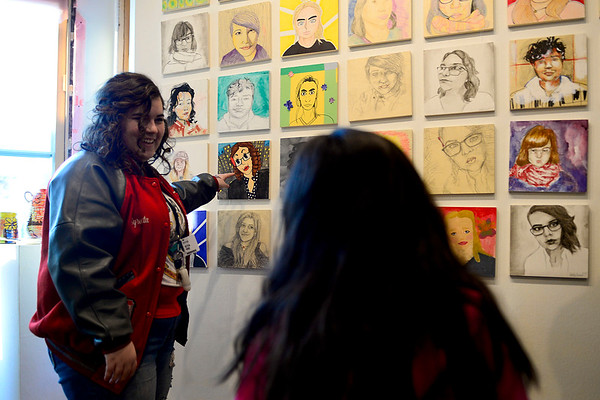 "BEN MIKESELL | THE GOSHEN NEWS<br /> Syreeta Moore, a senior at Goshen High School, shows off her portraits she made Friday at Goshen Youth Arts for the ""FACES: Portraits of our Community"" exhibit."