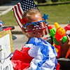 LEANDRA BEABOUT | THE GOSHEN NEWS<br /> Bailey Beehler, 7, Nappanee, sits surrounded by patriotic symbols in the Fourth of July parade in downtown Nappanee.