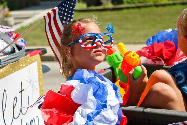 LEANDRA BEABOUT | THE GOSHEN NEWS<br /> Bailey Beehler, 7, Nappanee, gazes upward as she sits and waits to be a participant in the downtown Fourth of July parade.
