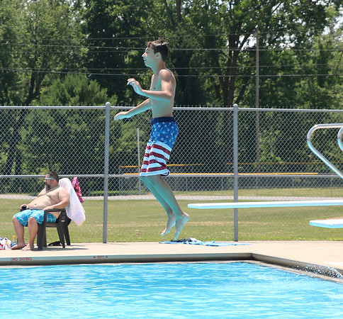 SHEILA SELMAN | THE GOSHEN NEWS<br /> Isaiah Parson, Goshen, jumps off the diving board at Shanklin Pool Sunday afternoon in Goshen. Temperatures soared into the 90s Sunday as the heat wave continued in northern Indiana.
