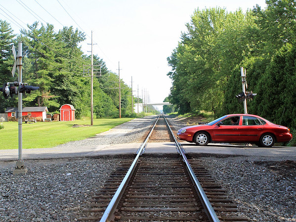 Roger Schneider | The Goshen News<br /> A car and driver cross the Marion Line railroad south of Goshen Monday. The crossing will be closed as part of the deal that allowed the Waterford Parkway bridge, in the background, to be constructed.