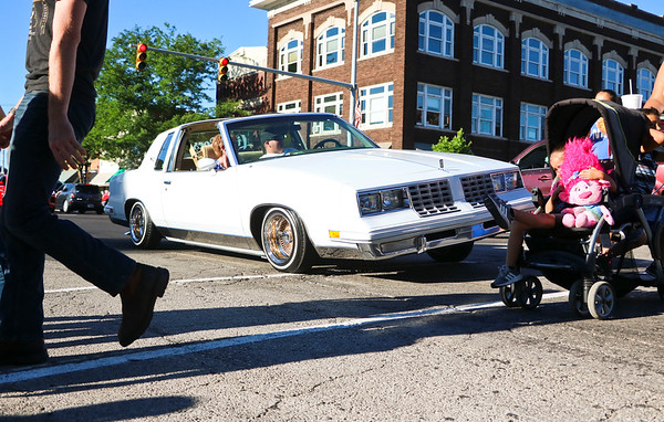LEANDRA BEABOUT | THE GOSHEN NEWS<br /> Pedestrians cross in front of a car on hydraulics during Goshen's Crusin' Reunion.