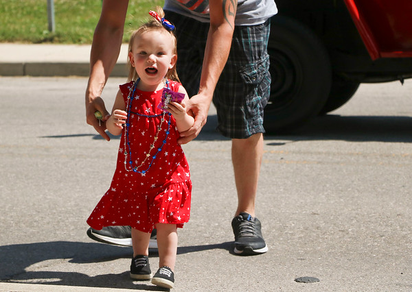 LEANDRA BEABOUT | THE GOSHEN NEWS<br /> Aubree Bicek, 1, Nappanee, excitedly returns to the sidewalk with candy that had been thrown out to spectators at Nappanee's annual Fourth of July parade.