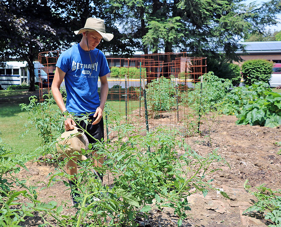 Kelby Youngberg, 16, waters the garden on Thursday, July 12.