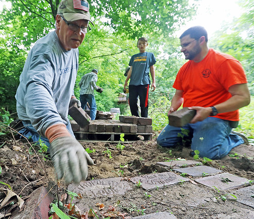 ROGER SCHNEIDER | THE GOSHEN NEWS<br /> Volunteers helped out the staff of the Elkhart County Parks Department's Boot Lake Nature Preserve Saturday morning. The volunteers removed paving bricks once used for a walkway and did other maintenance projects. According to the preserve's manager, Sherry Bowen, volunteers will again be needed in the fall when seeds will be collected at the 300-acre park's prairie. The park is located at 51430 C.R. 3, northwest of Elkhart. Pictured from left are Mark Dalrymple of Elkhart, Carter Gull, 13, and Matt Gull, both of Goshen.
