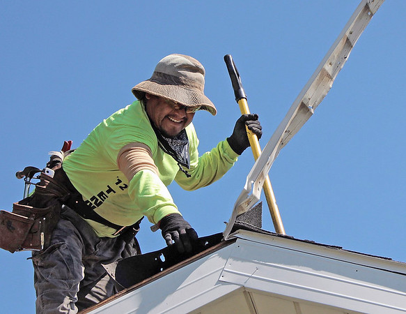 LIZ RIETH | THE GOSHEN NEWS Daniel Arrgue was contracted by Builders of Hope to give Melissa Hill's house in Goshen a new roof July 18.