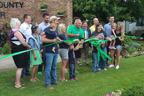 Roger Schneider   The Goshen News<br /> Mark Kritzman, president of the Elkhart County 4-H Fair Board, cuts the ribbon Friday morning to open this year's fair. Kritzman was assisted by his wife Diane, to his left and family members Josh Koontz holding Leighton Koontz, 11 months old, Karrin Koontz, Easton Koontz, 6, and Braxton Koontz, 4.