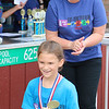 JOHN KLINE | THE GOSHEN NEWS<br /> Raegan Kaminer, 8, Bristol, smiles after accepting her first place trophy in the 7/8 Girls division of the 14th annual Kerry's Kids' & Teens' Try-Athlon in Goshen Saturday morning. Also pictured is Goshen Parks and Recreation Superintendent Tanya Heyde, who presented the award.