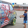 Denise Fedorow | The Goshen News<br /> Brothers Bryce and Xander (partially hidden) Knepp spray paint a van in unison at Jakal Leather/Bramble Supply Saturday. The van was part of a Community Paint-A-Van activity during Nappanee's first Art Walk.