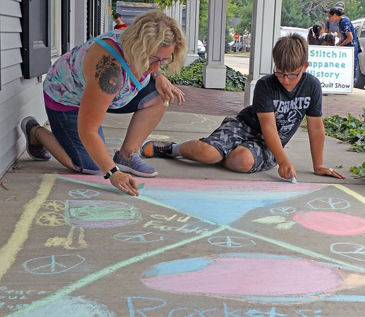 Denise Fedorow | The Goshen News<br /> Lindsay and Mason London create a collage of chalk art at the Nappanee Center Saturday as part of the first Nappanee Art Walk.