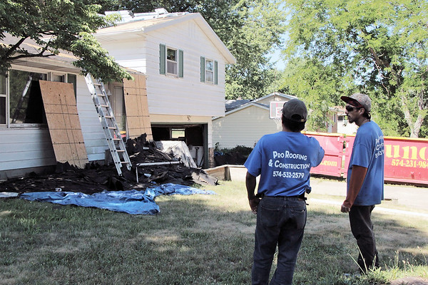 LIZ RIETH | THE GOSHEN NEWS Edwen Rios, left and Ruben Ramos were contracted by Builders of Hope to give Melissa Hill's house in Goshen a new roof July 18.