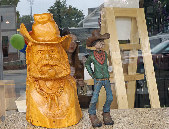 Denise Fedorow | The Goshen News<br /> A girls takes a peek at wood carvings created by Brian Yoder, who was working on a new cowboy piece while participating in the Nappanee Art Walk Saturday afternoon.