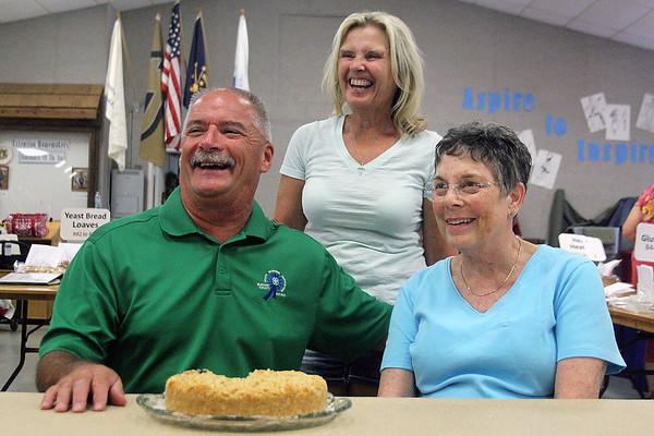 LIZ RIETH | THE GOSHEN NEWS Mark Kritzman, left, his wife Diane and Cheryl Baker pose for a photo. Baker's blueberry cheesecake crumb cake won the Elkhart County 4-H Fair president's baked item contest Thursday.