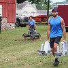 LIZ RIETH | THE GOSHEN NEWS Bertha Luna, Elkhart, and Dustin Snider, New Paris, compete in the farmer's walk event in the Elkhart County 4-H Fair Strongman Competition Saturday.
