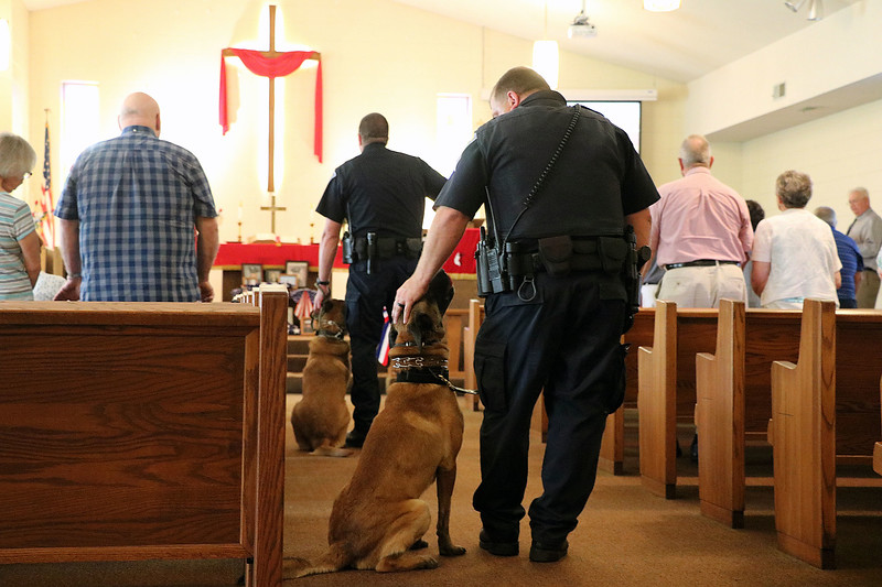 TERRAH HARMON | THE GOSHEN NEWS Master Trooper Dave Caswell reassures his K-9 companion, Chase, during the blessing service at Richmond United Methodist Church. Photo taken Thursday June 29, 2018.