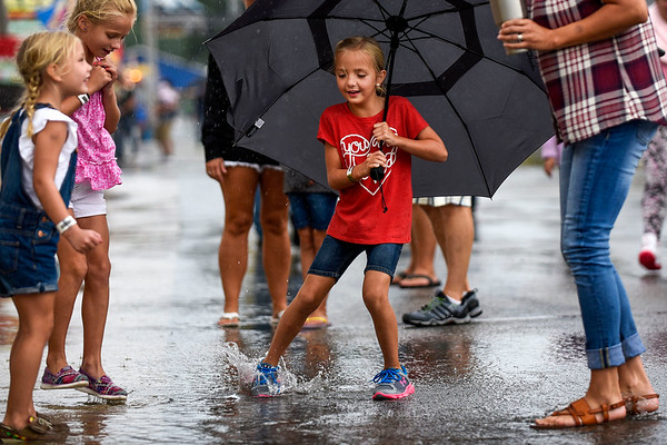 BEN MIKESELL | THE GOSHEN NEWS<br /> Spencer Wogoman, 6, from Millersburg, center, trots through puddles while her friends and mother, Liz Wogoman, watch on during the opening day of the Elkhart County 4-H Fair Friday. Friday's storms canceled or postponed many events scheduled throughout the evening. Rain is expected off and on throughout the weekend, and temperatures will be in the mid-70s, meteorologist Geoffrey Heidelberger at the National Weather Service said.