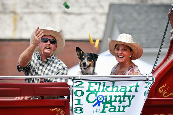 BEN MIKESELL | THE GOSHEN NEWS<br /> Rodeo members Aaron and Bobbie Platt throw candy to the crowd with their dog Maggie during the 2018 4-H Fair Parade Sunday in downtown Goshen.
