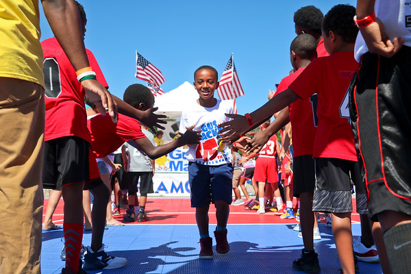LEANDRA BEABOUT | THE GOSHEN NEWS<br /> Tyren Matthews, 8, Elkhart, receives high fives as he runs onto the court for his three-on-three round in Saturday's Gus Macker Tournament in Elkhart.
