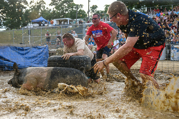 BEN MIKESELL | THE GOSHEN NEWS<br /> Rich Miotto, left, Chris Cage, center, and Austin Miotto, all from Warsaw, chase a pig around the tire during Thursday night's pig wrestling event at the Kosciusko County Fair in Warsaw. Teams were given 45 seconds to lift the pig out of the mud and touch it to the tire in the middle of the pen.