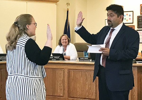 JOHN KLINE   THE GOSHEN NEWS<br /> Goshen School Board President Felipe Merino, right, conducts the swearing-in ceremony for new board member Amanda Qualls, left, during a meeting of the school board Monday evening. Qualls was elected by the board in June to replace former at-large member Jane DeVoe, who announced her resignation May 29.