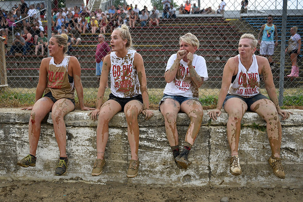 BEN MIKESELL | THE GOSHEN NEWS<br /> The members of Bacon Beaches from left, Sarah Toles, Alexis Lowe, Carla Lowe, all from Kendallville and Tammy Riner, visiting from Florida, watch from the sidelines as other teams try to catch a pig during Thursday night's pig wrestling event at the Kosciusko County Fair in Warsaw.
