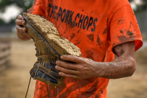 BEN MIKESELL | THE GOSHEN NEWS<br /> Jacob Tolson from Pierceton dumps mud from his boot after participating in Thursday night's pig wrestling event at the Kosciusko County Fair in Warsaw.