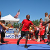 LEANDRA BEABOUT | THE GOSHEN NEWS<br /> Anthony Furlow, 10, receives high fives as he runs onto the court for his three-on-three round in Saturday's Gus Macker Tournament in Elkhart.