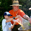 BEN MIKESELL | THE GOSHEN NEWS<br /> District committee member Bruce Miller helps Webelo Domenic Furfaro, 10, pour macaroni into a pot while learning how to cook during Cub Scout Day Camp Thursday at Ox Bow Park.