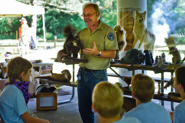 BEN MIKESELL | THE GOSHEN NEWS<br /> Naturalist Andy Langdon with the Elkhart County Parks Department explains behaviors of skunks to Webelos at a station during Cub Scout Day Camp Thursday at Ox Bow Park.