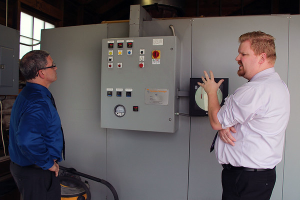 Funeral director Casey Miller, left and funeral director intern Michael Weaver control the crematory with the panel shown June 12.