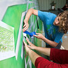 LEANDRA BEABOUT | THE GOSHEN NEWSJacob Beachey, 13, and his mom Carrie Beachey, both of Goshen, work on a mural inside a storage unit in Elkhart. Carrie, a local painter and fiber artist, was contracted by H&R Block in Bremen to create the giant piece for the business.