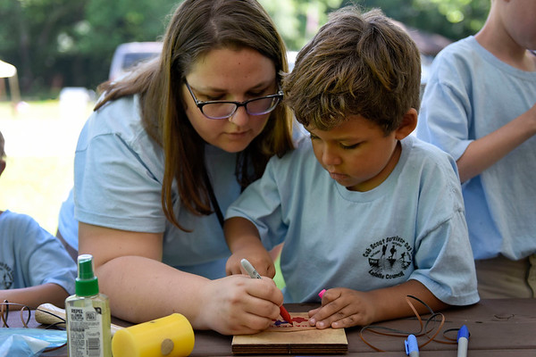 BEN MIKESELL | THE GOSHEN NEWS<br /> Amber Bentley, South Bend, helps her son Maddox, 7, with leather crafting during Cub Scout Day Camp Thursday at Ox Bow Park.