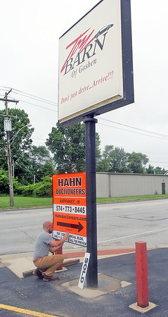 "ROGER SCHNEIDER | THE GOSHEN NEWS<br /> Clint Cripe of Hahn Auctioneers, prepares  Monday afternoon  to place a ""sold"" sign on the former The Toy Barn sign post at 711 W. Lincoln Ave. in Goshen."