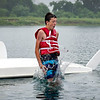 BEN MIKESELL | THE GOSHEN NEWS<br /> Eli Hochstedler, 14, Goshen, jumps into the water to flip his capsized boat during Sail Camp Wednesday morning at Fidler Pond.