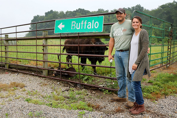 LIZ RIETH | THE GOSHEN NEWS <br /> Peter and Erica Cook stand next to their bison ranch Wednesday in Wolcottville. The couple started Cook's Bison Ranch in 1998.