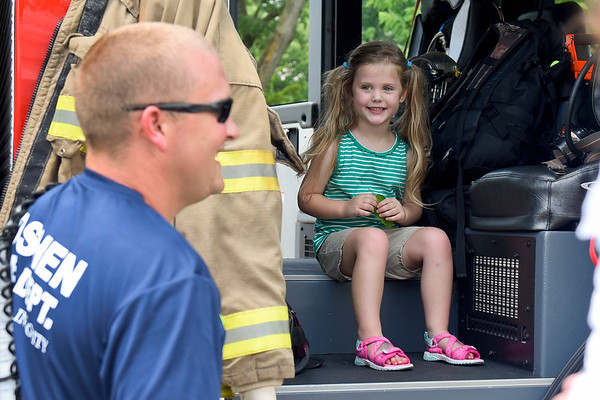 BEN MIKESELL | THE GOSHEN NEWS<br /> Ellie Lawson, 4, Goshen, smiles from the comfort of a Goshen Fire Engine during Touch a Truck Monday afternoon in the parking lot of the Goshen Public Library. During the hour-long event, a fire truck, RV and boat were on display for children to tour.