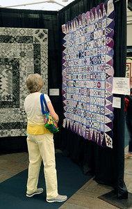 JOHN KLINE | THE GOSHEN NEWS Sandee Walaszek, of Westchester, Illinois, examines one of the hundreds of quilts available for viewing during the 2018 Shipshewana Quilt Festival Saturday afternoon.