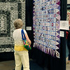 JOHN KLINE | THE GOSHEN NEWS<br /> Sandee Walaszek, of Westchester, Illinois, examines one of the hundreds of quilts available for viewing during the 2018 Shipshewana Quilt Festival Saturday afternoon.