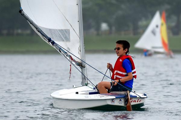 BEN MIKESELL | THE GOSHEN NEWS<br /> David Stutzman, 11, Goshen, adjusts his sail during Sail Camp Wednesay morning at Fidler Pond in Goshen.