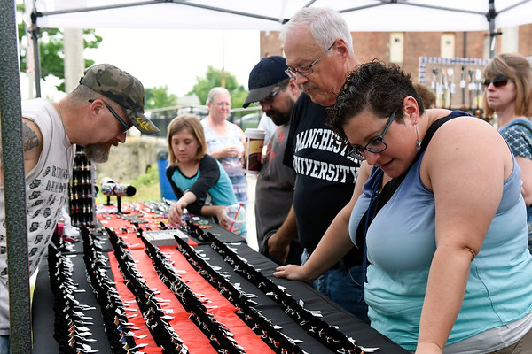 BEN MIKESELL | THE GOSHEN NEWS<br /> Arts on the Millrace attendees look at jewelry for sale at the Dead President Coin Rings tent, one of more than 35 tents during Saturday's event in downtown Goshen.
