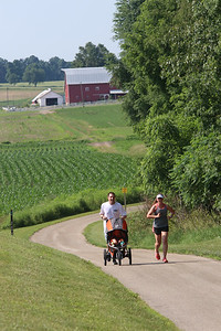 Roger Schneider | The Goshen News Ryan and Sally Boring, Elkhart, job along the Pumpkinve Nature Trail with their son Royce, 8-months-old, on June 16, 2018. The couple were running up the hill north of C.R. 127.