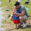 Roger Schneider| The Goshen News<br /> Jared Miller of Elkhart helps his son Collin, 2, reel in a bluegill during the fishing tournament Saturday at Fidler Pond Park in Goshen.